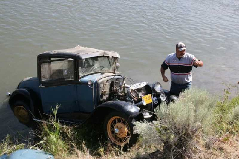 by: PHOTOS CONTRIBUTED BY PRINEVILLE POLICE DEPARTMENT - A 1930 Ford Model A vehicle belonging to Prineville residents was stolen by a transient and crashed into the Crooked River south of Prineville. In the above photo, an employee with STAR Towing carefully retrieves the car from the river.