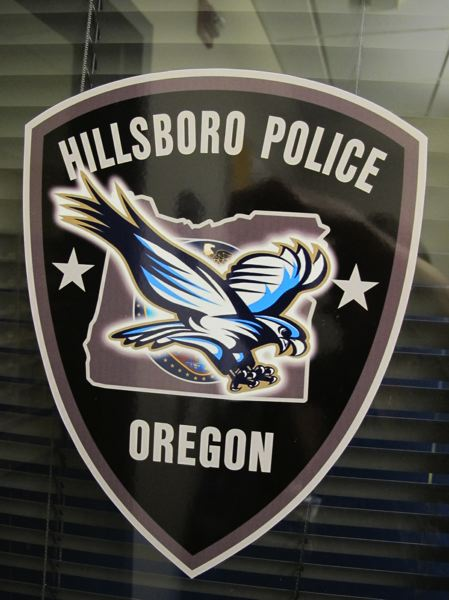 by: HILLSBORO TRIBUNE PHOTO: KATHY FULLER - Because he serves at Liberty High School much of the time, Emory Souza modified the Hillsboro Police department badge on the window of his Liberty office to incorporate Libertys logo of the schools mascot, a flying falcon.