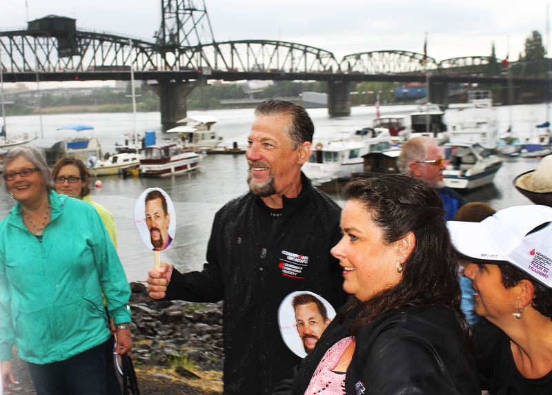 by: OUTLOOK PHOTO: CARI HACHMANN - Standing among supporters, friends and family, Hall smiles for a camera on the Portland waterfront.