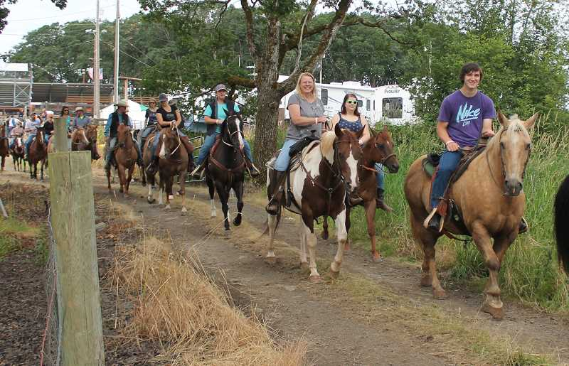 by: JIM BESEDA/MOLALLA PIONEER - The second group of riders heads out from the rodeo grounds Sunday morning during the annual Molalla Buckeroo Trail Ride.