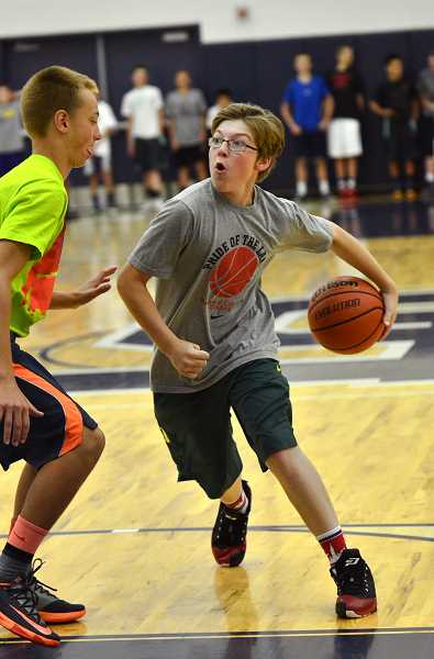by: REVIEW PHOTO: VERN UYETAKE - Mike Mercep drive to the basket during basketball camp at Lake Oswego High School.
