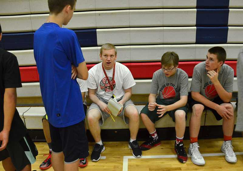 by: REVIEW PHOTO: VERN UYETAKE - Camp assistant Cory Coombe, center, talks with a group of basketball players during a break in the action.