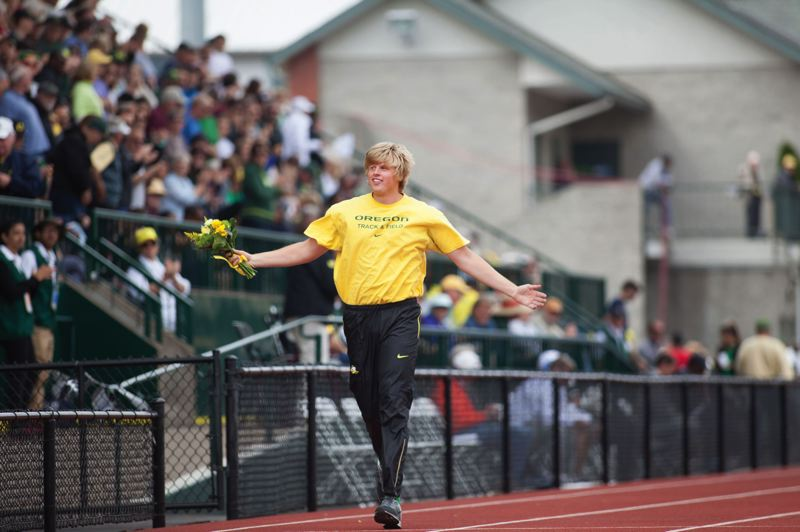 by: PAMPLIN MEDIA GROUP: KEVIN HARDEN - Gresham High graduate Sam Crouser takes a victory lap around Hayward Field after winning the javelin at this years NCAA championship meet.