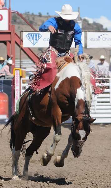 by: LON AUSTIN/CENTRAL OREGONIAN - Brady Nicholes of Hoytsville, Utah rides James Bond Sunday afternoon. NIchols finished second in the saddle bronc riding competition with a score of 81