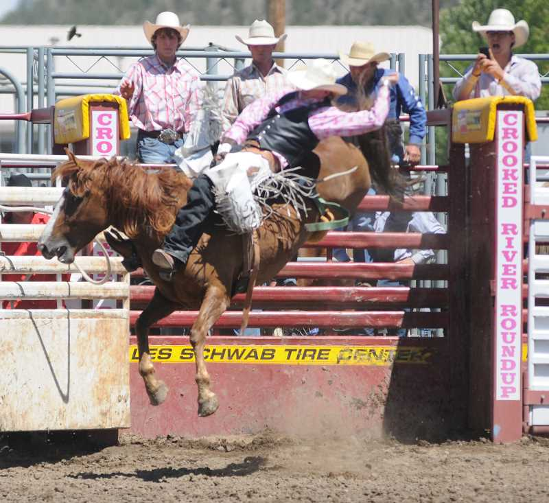 by: LON AUSTIN/CENTRAL OREGONIAN - Wyatt Bloom comes out of the chute during Sunday's Crooked River Roundup. Bloom, of Bend, won the bareback competition riding Flying Diamond Rodeo's No. 13 for a score of 80.