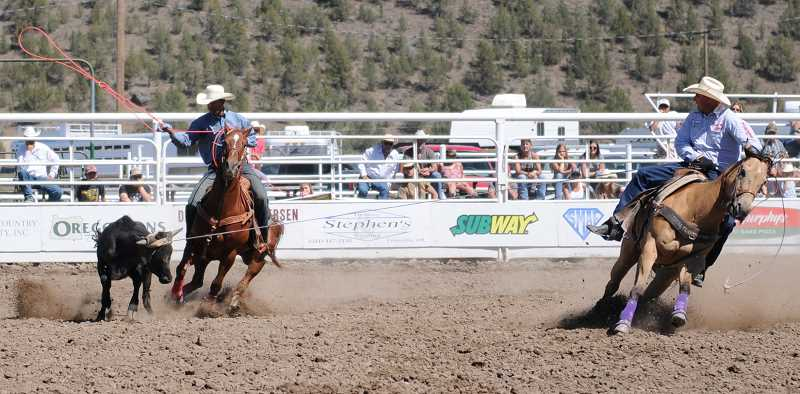 by: LON AUSTIN/CENTRAL OREGONIAN - Jake Barnes (Right) and Junior Nogueira finish their second go round of team roping with a time of 5.7 seconds. Barnes of Scottsdale, Ariz. and Nogueira, from Brazil, won the averageat the rodeo with a total time of 11.4 seconds on two heads.