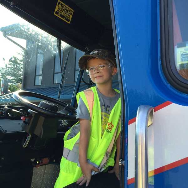 by: KRISTEN FEUZ - Mason DeBruyn gets ready to go on a ride in a garbage truck at Republic Services last week.