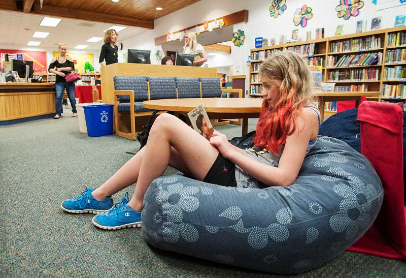 by: SPOKESMAN PHOTO: JOSH KULLA - Wilsonville student Emily Stott will be going into the fifth grade this fall at Boones Ferry Primary. She is a longtime participant in the Wilsonville Librarys summer reading program and visits the library every week. 'Oh yeah, I do it every year,' she said.