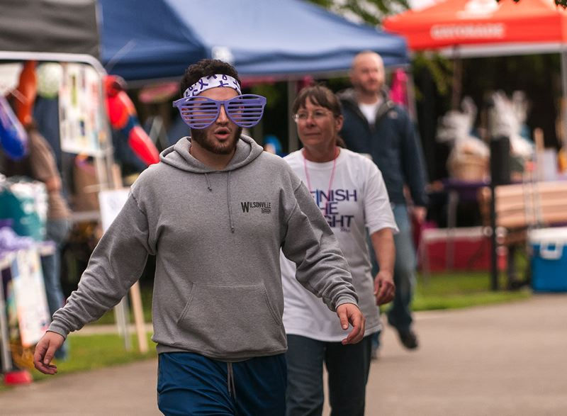 by: SPOKESMAN PHOTO: JOSH KULLA - Team Cancer Avengers! member Colton Holly has fun while walking a lap during the 2014 Wilsonville Relay for Life in Town Center Park.