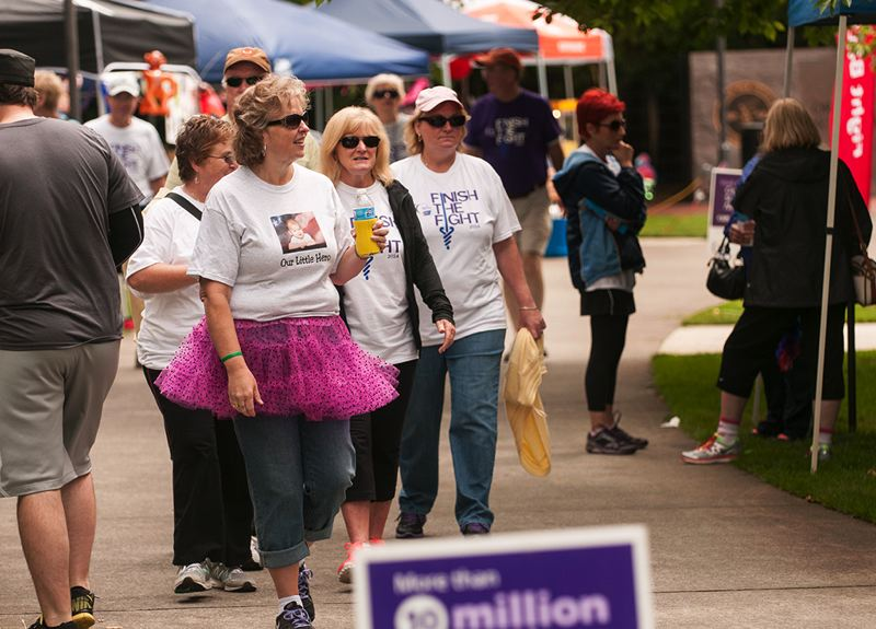 by: SPOKESMAN PHOTO: JOSH KULLA - Kim Smith of Team Crimson Trace (pink tutu) walks with other team members Saturday morning at the Wilsonville Relay for Life.