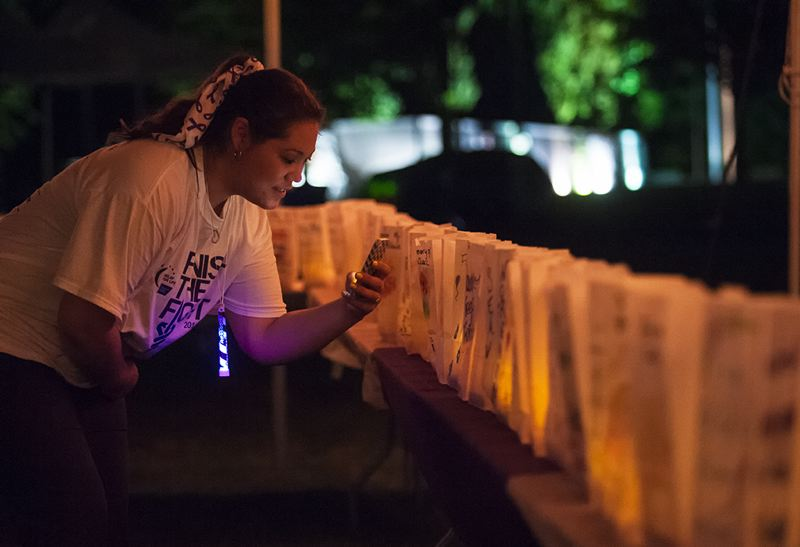by: SPOKESMAN PHOTO: JOSH KULLA - Mayumi Norquist of Team Cancer Avengers! takes a photo of glowing luminaria set out to commemorate victims and survivors of cancer. Each bag contains a candle inside and the name of a victim or suvivor on the outside.