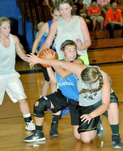 by: SETH GORDON - Nose for the ball - Newberg sophomore Savanna Milroy fights for a loose ball during a  summer league basketball game June 25 at St. Paul High School.