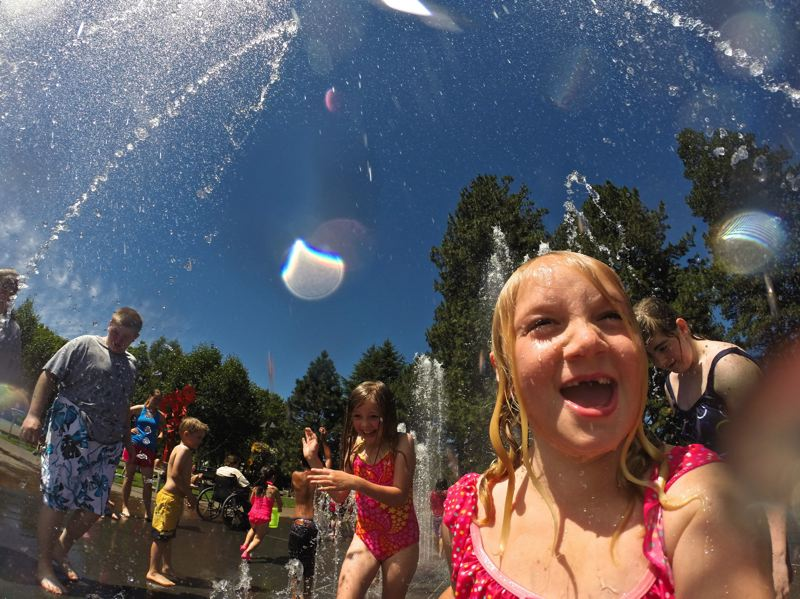 by: TRIBUNE PHOTO: JAIME VALDEZ - Alyssa Dietz, 5, of Beaverton, drenches herself in the Beaverton City Fountain Park while holding a Gopro camera during Tuesday afternoon's hot weather.