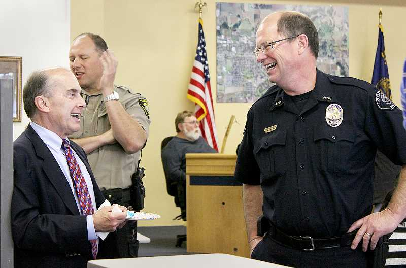 by: SUBMITTED - Retiring, again - Cornelius Police Chief Ken Summers (right) shares a laugh with City Manager Rob Drake at a goodbye party in his honor. His last day as chief was June 30.
