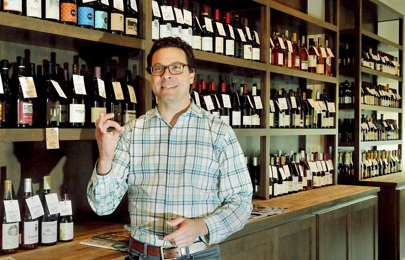 by: GARY ALLEN - Variety - Valley Wine Merchants owner Andrew Turner stands amid just some of the wines he offers at his College Street Shop.