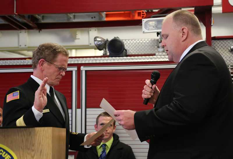 by: MALLORY GWYNN - New Canby Fire Chief James Davis is sworn in by Aaron Branum, chairman of district board of directors.
