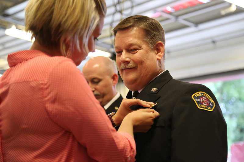 by: MALLORY GWYNN - Kunze's daughter, Stephanie Anderson pins on his retired chief badge during the end of watch ceremony.