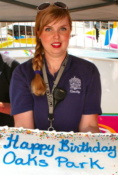 by: DAVID F. ASHTON - Oaks Amusement Parks Events Manager, Emily McKay, shows THE BEE one of the massive birthday cakes about to be served to park guests.