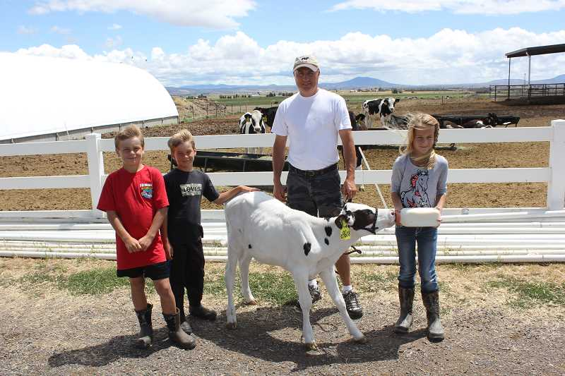 by: SUSAN MATHENY/MADRAS PIONEER - Jos Poland and his kids Johan, left, Maikel and Maija, right, feed a calf at the dairy.