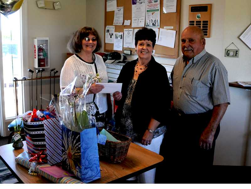 by: BILL VOLLMER PHOTO - Patty Lieuallen, left, presents gifts to Sharon and Fritz Marvel at their retirement party.