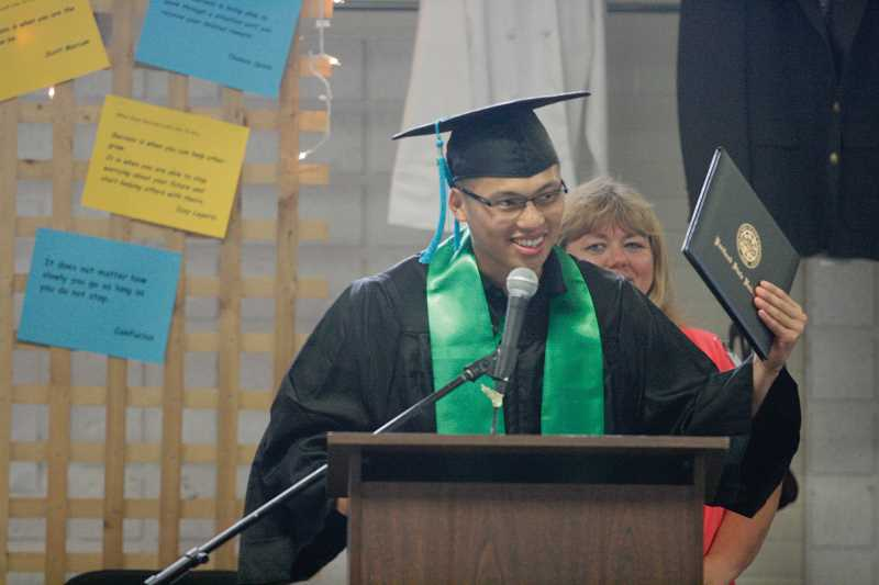 by: PHIL HAWKINS - Sang Dao, of MacLaren Youth Correctional Facility, holds aloft his bachelor's degree in criminology from Portland State University as he speaks to his fellow graduates at Wednesday's graduation ceremony.