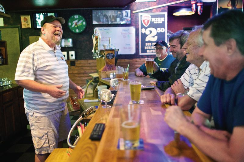 by: TIMES PHOTO: JAIME VALDEZ - Steve Michaud, owner of Scottys sports bar on Southwest Scholls Ferry Road, shares a moment with friends who have been customers for years. Michaud has gone nearly five years without a recurrence of the brain cancer that sent him to surgery, a chemotherapy regimen and most recently a clinical trial study of an experimental vaccine.