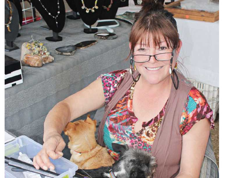 by: HOLLY M. GILL - Sandra Moar beads a bracelet while two of her dogs rest in her lap. Moar and Dean Banks, of Happy Valley, returned to the Rockhounds show at the fairgrounds for the second year.