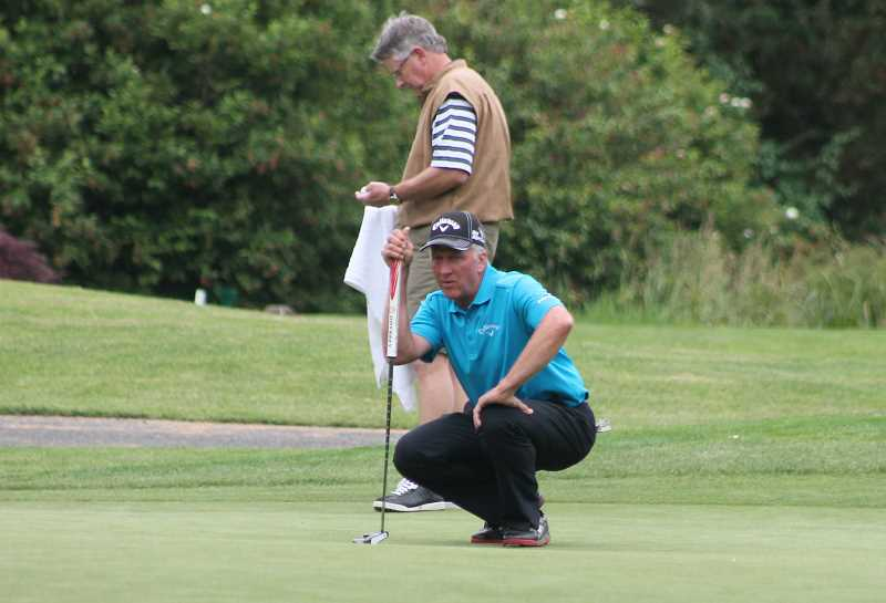 by: JIM BESEDA/MOLALLA PIONEEER - Arrowhead head pro Rob Gibbons lines up a putt during his playoff with Brad Faller at last month's Callaway Golf Invitational at Arrowhead Golf Club.