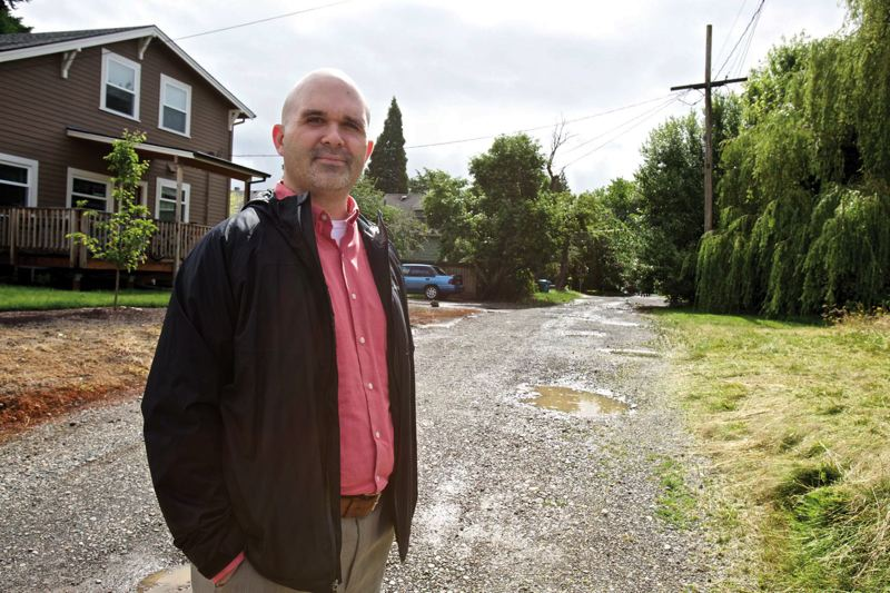 by: TRIBUNE PHOTO: JAIME VALDEZ - Tim Cowan, who has owned a home on North Oberlin Avenue near the University of Portland since 2003, tried but failed to enlist a majority of his neighbors to agree to put up money to pave the street and add a sidewalk.