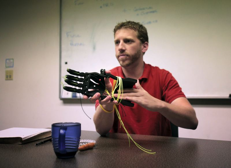 by: TRIBUNE PHOTO: JONATHAN HOUSE - 3D printed prosthetic hands can be manufactured quickly, cheaply and to perfectly fit. Need a larger size? Just print a new one. Here Kristofer Beem of Portland-based RapidMade displays a hand his firm printed for an Astoria youth
