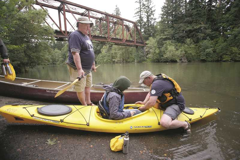 by: TIMES PHOTO: JONATHAN HOUSE - Discovery Day volunteers Dave Summers, left, and Richard Harrold help folks get into their kayaks and canoes on the Tualatin River.