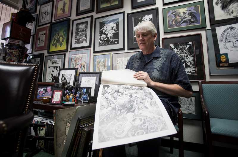 by: TIMES PHOTO: JONATHAN HOUSE - Mike Richardson, president and founder of Dark Horse Comics, shows off the original artwork of one of his newest graphic novels, Atomic League, in his downtown Milwaukie office.
