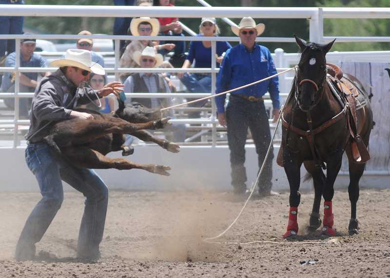 by: LON AUSTIN/CENTRAL OREGONIAN - Tuf Cooper works to turn his calf during a tie-down run at the Roundup. Cooper won the first go round and the average in the event.