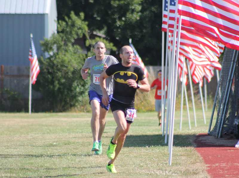 by: JIM BESEDA/MOLALLA PIONEER - Francis Stanbury of Redmond, Wash., surged past Beaverton's Eric Barten and into the lead about 400 meters from the finish of Friday's 3rd annual Freedom 5k at Heckard Field in Molalla.