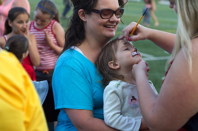 by: LACEY JACOBY - Sarah Dougall gets transformed into a cat at the Old Fashioned 4th of July Celebration at Tigard High School.