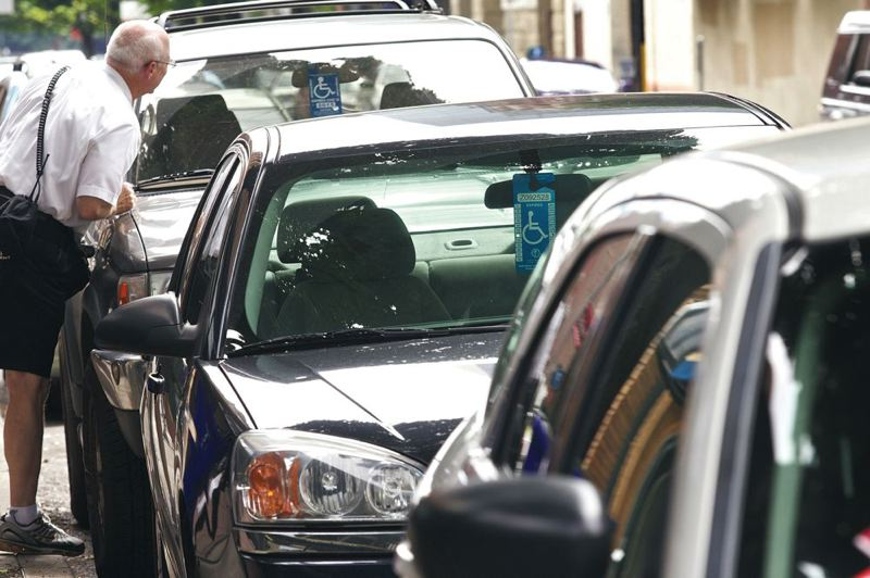 by: TRIBUNE FILE PHOTO: JAIME VALDEZ - Parking code enforcement officer Gary Shervey checked last summer the number on a disability placard on Southwest Taylor Street. New city disabled parking rules mean many drivers with disability placards still have to pay parking meters to park in downtown.