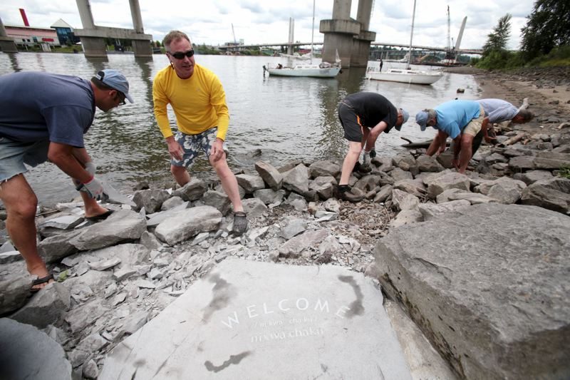 by: TRIBUNE PHOTO: JONATHAN HOUSE - From left, Willie Levenson, Andy Jansky, Tom Vandel, Tod Cordill and John Ostrander help move rocks and clean up the new area at Poets Beach in downtown Portland.