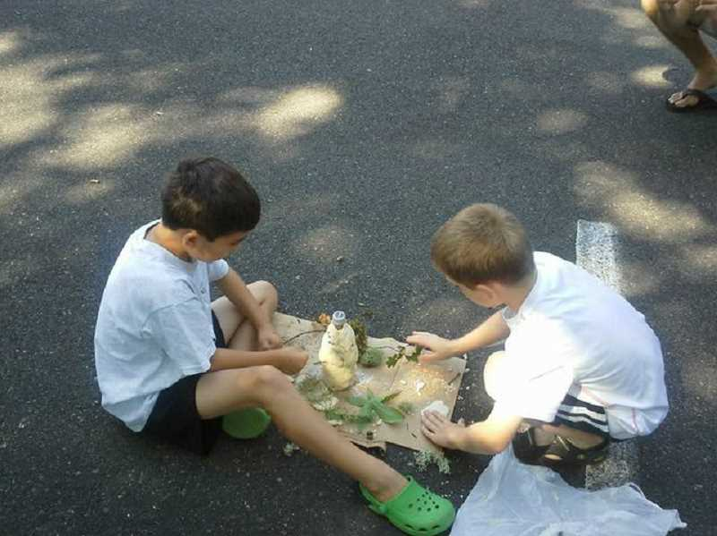 by: SUBMITTED PHOTO - Mathew Teem and Evan Carillo work together to make a volcano at Camp Kensington in the summer of 2013.