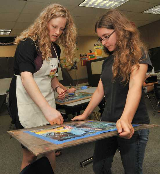 by: SPOKESMAN FILE PHOTO: VERN UYETAKE - MacKenzie Weber receives instruction from Amber Sprague on her collage during the 2013 Childrens Art Institute.