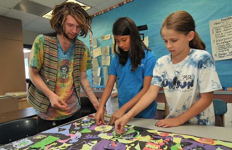 by: SPOKESMAN FILE PHOTO: VERN UYETAKE - From left, Dillon Silva instructs Julia Winkle and Maura Schramm on their cut-paper collage mural at the Childrens Art Institute last summer.