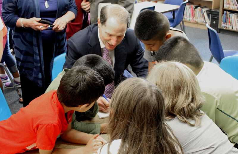 by: TYLER FRANCKE | WOODBURN INDEPENDENT - Sen. Ron Wyden signs autographs for children at the Nellie Muir Elementary School following a book reading there last Wednesday.