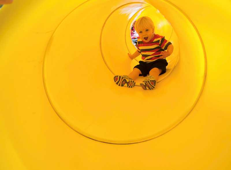 Chase Rossberg, 2, zips down the slide tube in the Wait Park playground. He is the son of Kari and Peyton Rossberg, of Canby.