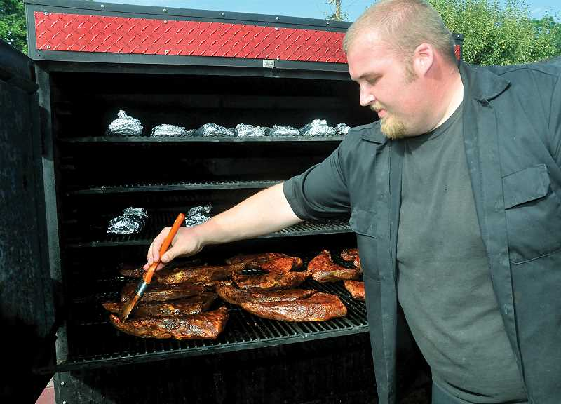 by: GARY ALLEN - Brandon Toedtemierer, of Slicks Big Time BBQ, bastes meat following the barbecue contest Friday at the St. Paul Rodeo.