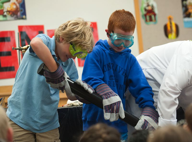 by: SPOKESMAN PHOTO: JOSH KULLA - Tualatin resident Henry Findtner joins Wilsonvilles Chase Crouch (right) in a science experiment July 3 at the Wilsonville Library, part of a Mad Science show for the librarys summer reading program.