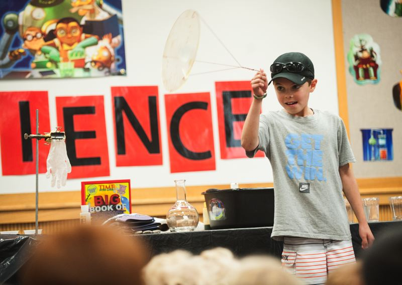 by: SPOKESMAN PHOTO: JOSH KULLA - Caden Mesdag of Wilsonville tries to spin a tray with a cup of water on it as a demonstration last week at the Wilsonville Librarys presentation of Mad Science.