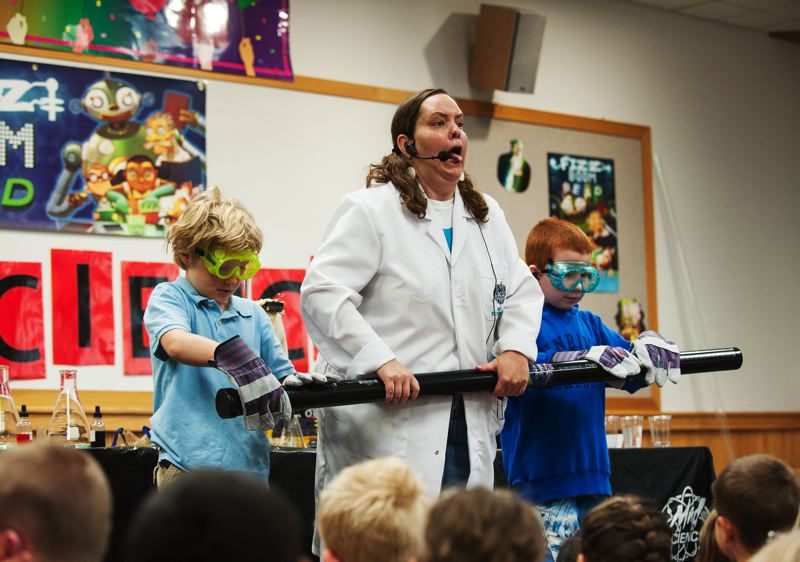 by: SPOKESMAN PHOTO: JOSH KULLA - Tiffany Musgrove of Mad Science leads Henry Findtner of Tualatin and Chase Crouch of Wilsonville in a science experiment July 3 at the Wilsonville Library.