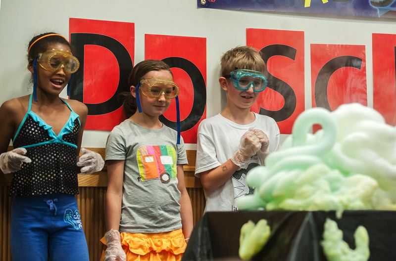 by: SPOKESMAN PHOTO: JOSH KULLA - Basic chemical reactions are a core part of Mad Science and its presentations for kids. Here, Ayanna Keys of Wilsonville (left) and two other volunteers watch a chemical reaction unfold before their eyes.