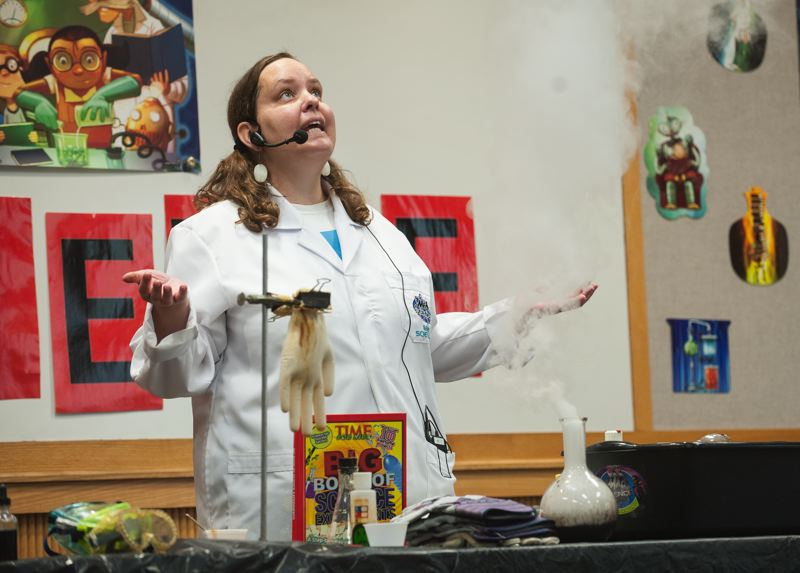 by: SPOKESMAN PHOTO: JOSH KULLA - Tiffany Musgrove of Mad Science performs July 3 at the Wilsonville Library.