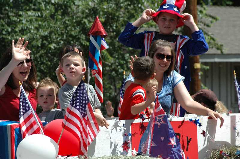 by: SUSAN MATHENY/MADRAS PIONEER - Moms and kids on the Deer Ridge Correctional Institution's float greet the crowd.