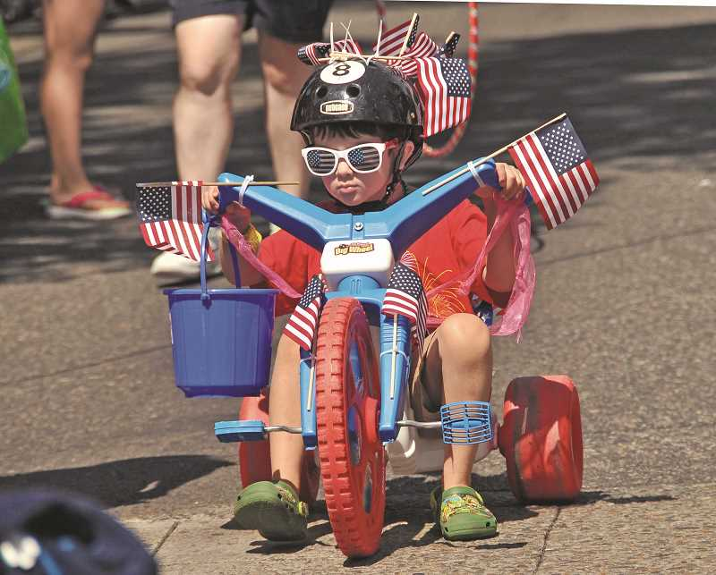 by: REVIEW PHOTO: VERN UYETAKE - Henry Harris pedals his three-wheeler down A Avenue in Lake Oswegos Star Spangled Parade.